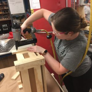 A student drills together a wooden crate.