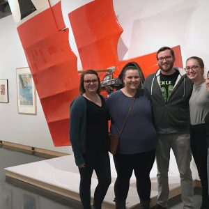 Students pose in front an art piece.