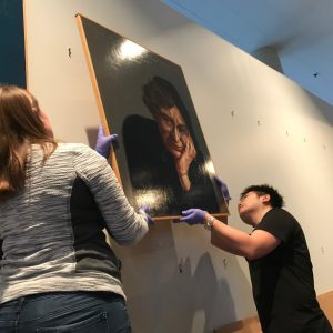 Students hang a painting.
