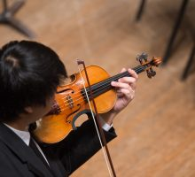 A student practices on his violin before a performance.