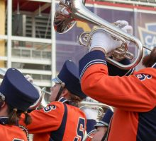 Syracuse University Marching Band horn players play to the fans in the seats