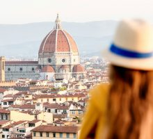 Student looking on the old town of Florence from Michelangelo square in the morning in Italy.