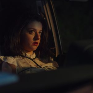 A girl sits in a dark car.