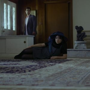 A girl lies on the carpet while a man looks out the window behind her.